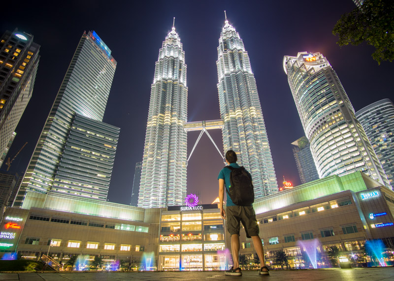 living as a nomad - petronas towers at night asian man