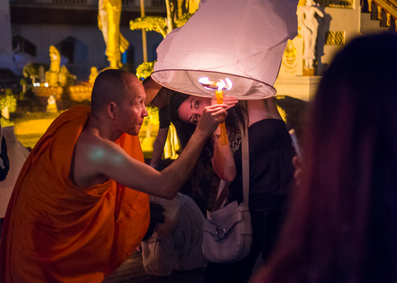 Loy Krathong Chiang Mai lantern festival - monk lighting up lantern
