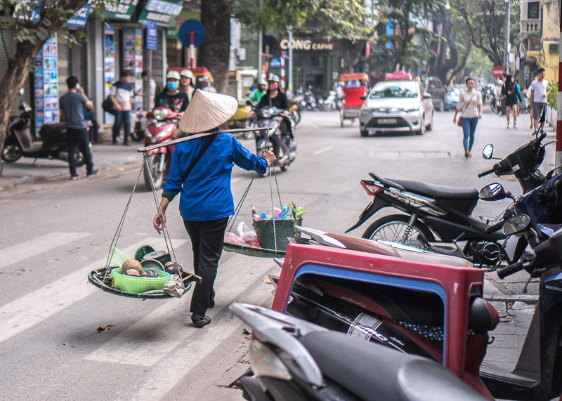 Hanoi travel blog - fruit vendor walking on street